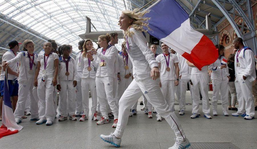 Médaillée de bronze en taekwondo, Marlène Harnois brandit le drapeau tricolore dans la gare de Saint-Pancras, à Londres, avant de prendre le train pour la France, lundi.