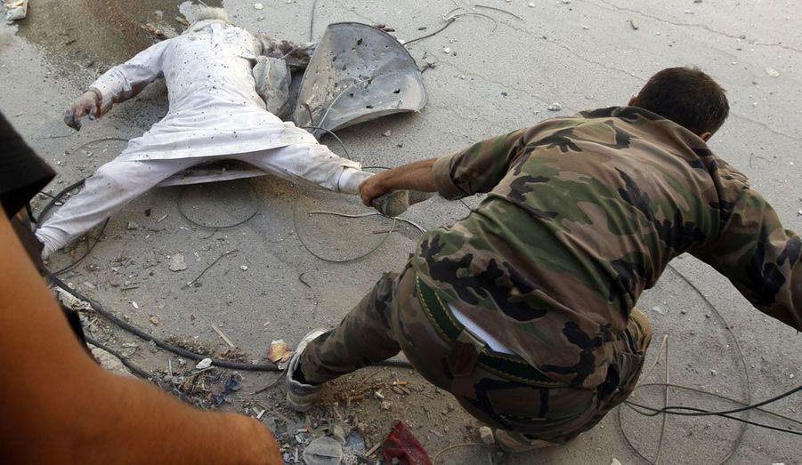 A Alep, en Syrie, un insurgé tire le corps de son camarade qui a été tué par un sniper loyaliste, selon les combattants de l'Armée syrienne libre.