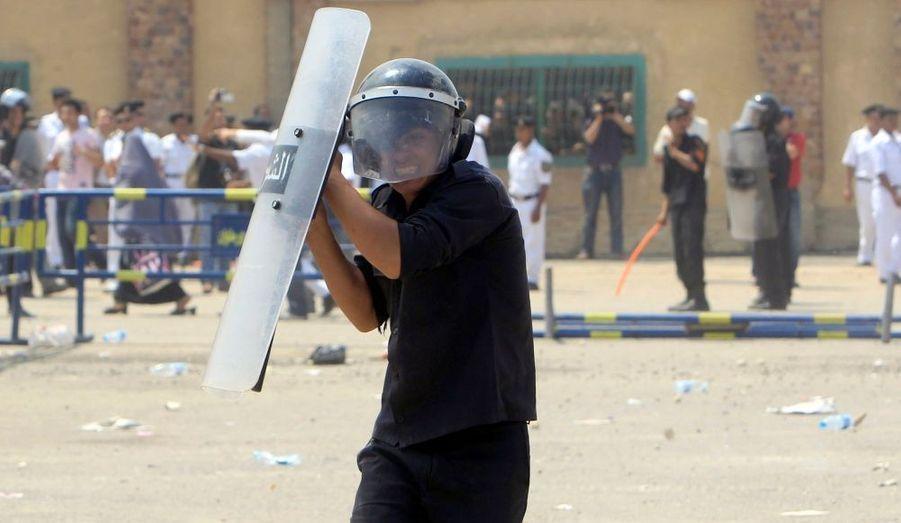 Un policier anti-émeutes se protège, pris dans des combats entre pro et anti-Moubarak devant l'Académie de Police du Caire, où l'ancien dictateur égyptien est jugé.