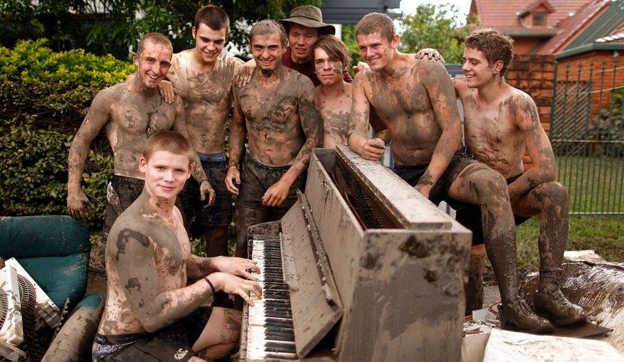Des amis posent devant un piano détruit par les eaux à Brisbane, en Australie. Les inondations qui ont débuté avant Noël ont fait au moins 19 morts et plus de 60 disparus dans l'état du Queensland.