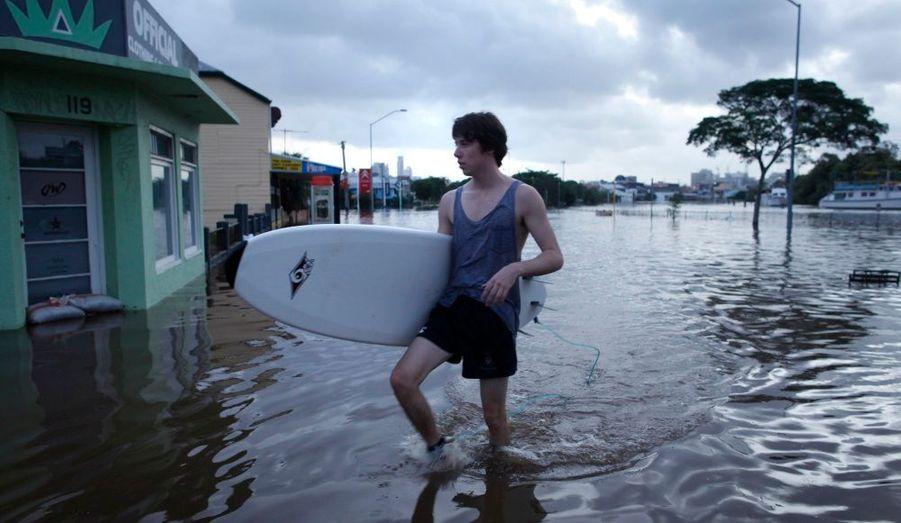 Un habitant de Brisbane marche dans la ville, planche de surf à la main. Les inondations en Australie ont causé 14 morts dans le pays depuis lundi.