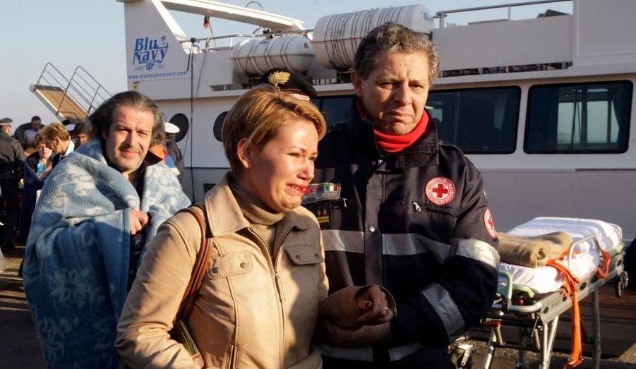 Les secouristes aident une femme à Porto Santo Stefano. Un bateau de croisière s'est échoué dans la nuit de vendredi à samedi au large de la Toscane, faisant quatre victimes et plusieurs disparus.