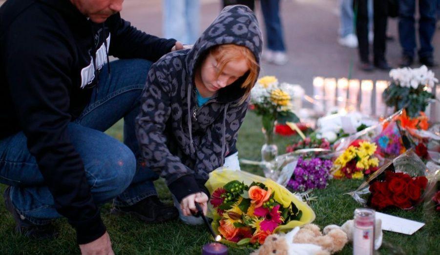 Une jeune fille et son père déposent une bougie devant l'hôpital où se rétablissent les victimes de la fusillade de Tuscon, en Arizona, qui a fait six morts et 14 blessés samedi dernier.