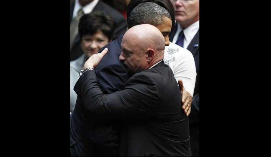 """Barack Obama s'est rendu mercredi au chevet de Gabrielle Giffords, l'élue grièvement blessée à la tête lors d'une fusillade, à l'entame d'un déplacement chargé d'émotion en Arizona. Peu après son atterrissage à Tucson, le président américain s'est immédiatement rendu à l'hôpital universitaire où est soignée la démocrate de 40 ans, prise pour cible lors d'une rencontre avec des électeurs samedi sur un parking. Il a ensuite prononcé un discours lors d'une cérémonie en hommage aux six personnes tuées et aux 14 autres blessées par Jared Lee Loughner, un jeune homme de 22 ans. """"Aucun de nous ne peut savoir exactement ce qui a déclenché cette attaque brutale. Aucun de nous ne peut savoir avec certitude ce qui aurait pu empêcher ces coups de feu d'être tirés ni quelles pensées se cachaient dans les tréfonds du cerveau de cet homme violent"""", a-t-il déclaré. Sur la photo, il serre dans ses bras Mark Kelly, le mari de Gabrielle Giffords."""