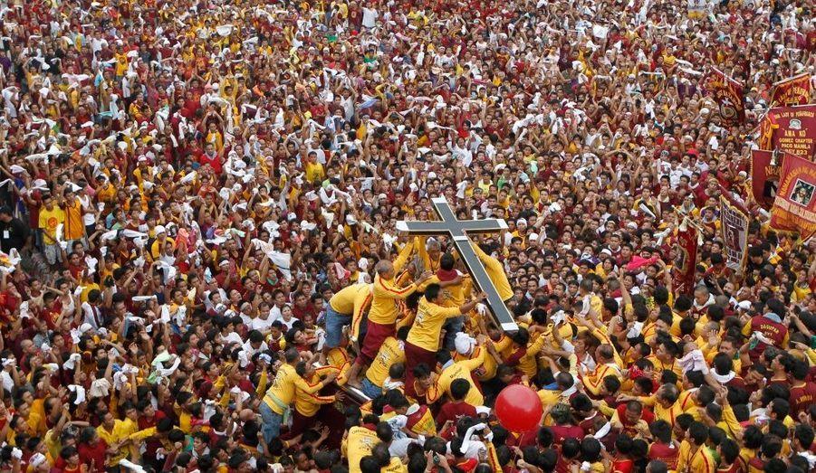 Des fidèles portent une croix géante avant le début d'une procession religieuse annuelle à Manille, aux Philippines. Les policiers ont déclaré qu'un million de fidèles était à Manille pour espérer voir ou toucher la statue noire de Jésus. Elle est supposée provoquer des miracles.