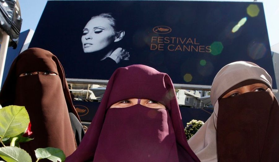 Trois femmes portant le niqab posent devant le Palais du Festival, à Cannes. Elles profitent de cette 64e édition pour protester contre la loi interdisant le port du voile intégral en France. L'hexagone est le premier pays européen à mettre en application cette loi. Ces trois femmes risquent une amende de 150 euros.