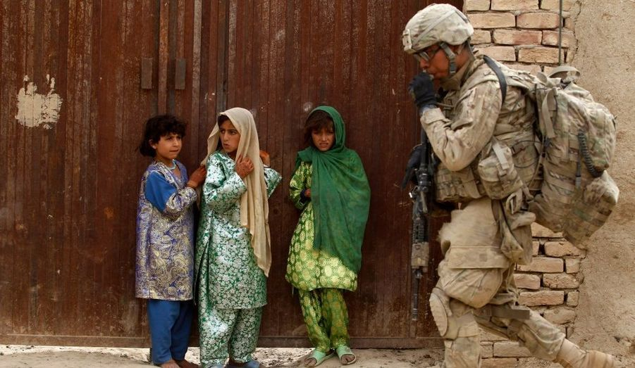 Des petites filles afghanes regardent passer un soldat de l'armée américaine appartenant à la 82ème division aéroportée lors d'une mission dans le district de Zhary, dans la province de Kandahar.