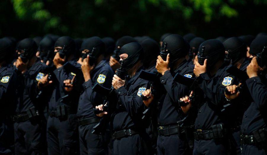 Des officiers de polices cagoulés se tiennent debout au cours d'une cérémonie de graduation à Comalapa au Salvador. Cette troupe d'élite a été spécialement formée pour lutter contre la violence des gangs dans le pays.