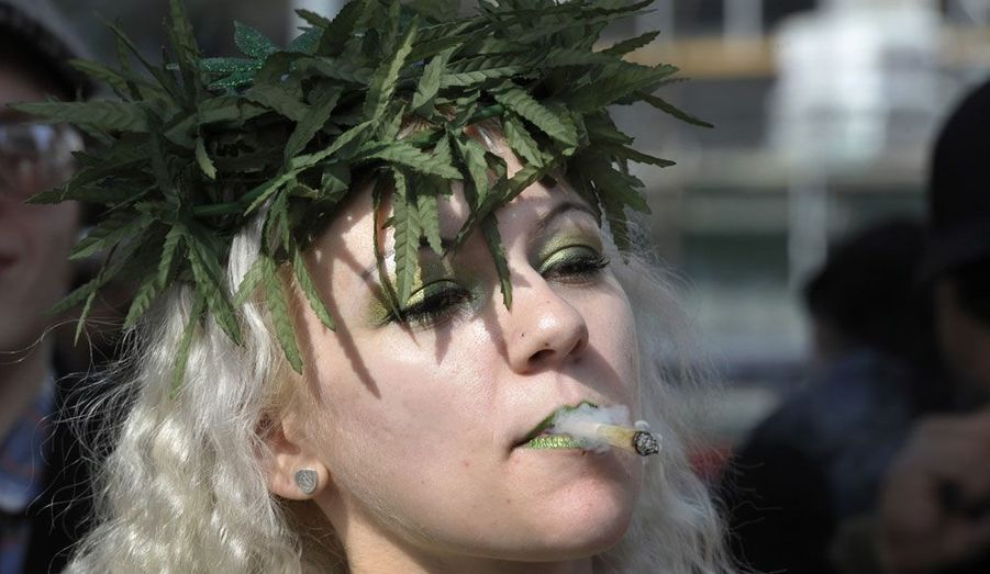 Une jeune femme fume du cannabis à Toronto, lors d'une manifestation annuelle pour réclamer la légalisation de cette drogue au Canada.