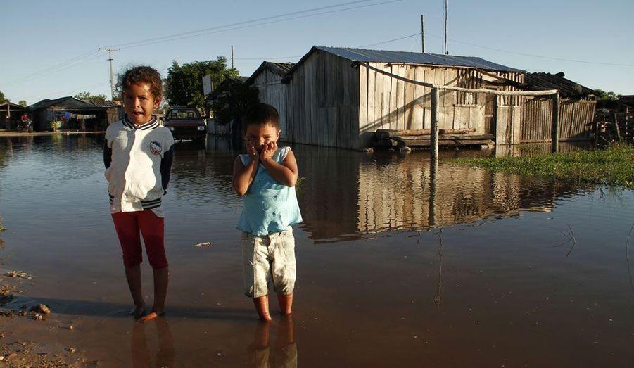 Deux enfants se tiennent debout dans l'eau après une inondation survenue dans la ville de Diaz, à 260 kilomètres d'Asuncion au Paraguay. Le gouvernement du pays a déclaré l'état d'urgence dans la zone touchée.