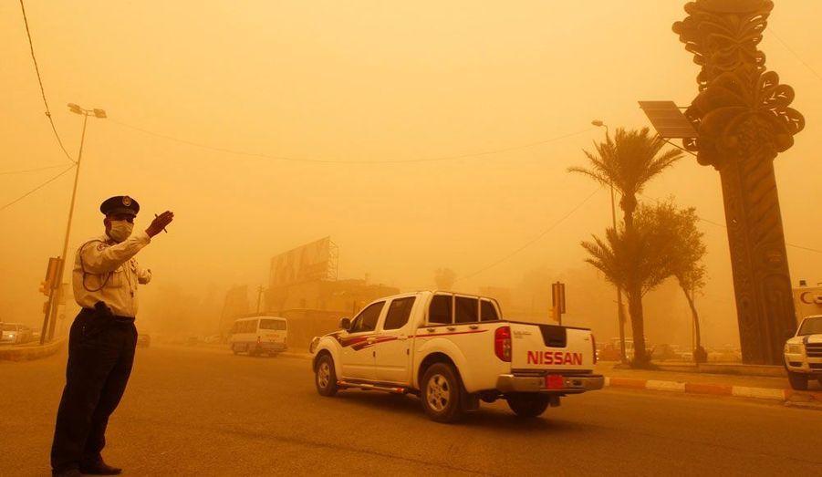 Un policier fait la circulation au cours d'une tempête de sable dans le quartier de Karrada à Bagdad.