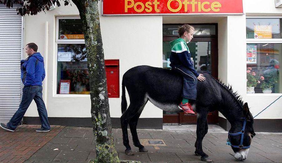 Cet enfant, assis sur un âne, attend devant le bureau de poste la fin de la vente d'ânes organisée à Irvinestown, en Irlande du Nord.