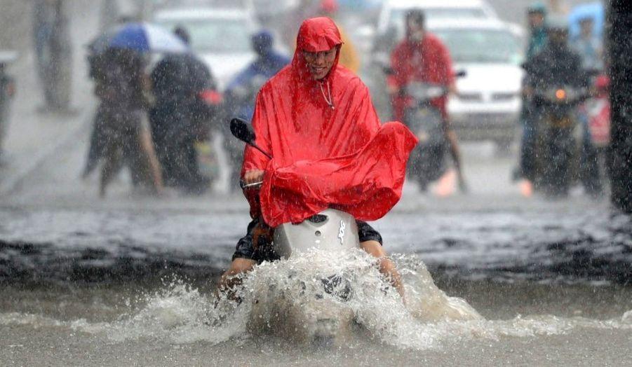 Un homme circule en vélo électrique dans une rue inondée à Nanjing, dans la province du Jiangsu, en Chine.