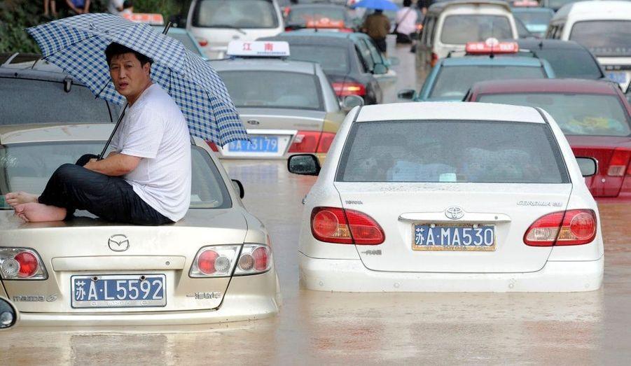 Un homme tient un parapluie, assis sur le coffre de sa voiture, paralysée par les inondations. Des pluies torrentielles touchent la province du Jiangsu, en Chine, sans interruption depuis quatre jours.