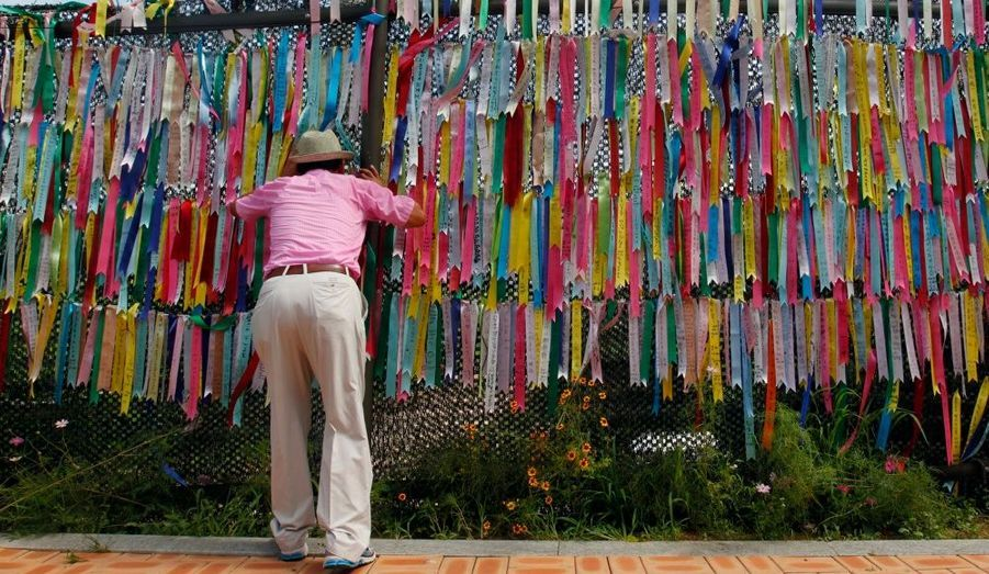 """Un homme regarde à travers une clôture de fil de fer barbelé sur lequel des rubans sont accrochés. Des vœux de réunification entre la Corée du Nord et la Corée du Sud sont inscris dessus. Le lieu de """"recueillement"""" est situé au pavillon Imjingak près de la zone démilitarisée séparant les deux Corées."""