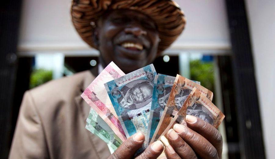 Un homme montre fièrement des billets de la nouvelle monnaie en cours au Sud-Soudan, pays créé il y a 10 jours, à la sortie d'une banque dans la capitale de Juba.