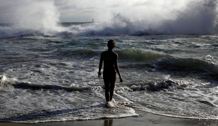Une femme téméraire brave les vagues de Venice Beach à Los Angeles en Californie alors qu'une tempête venant de l'hémisphère sud fait rage.
