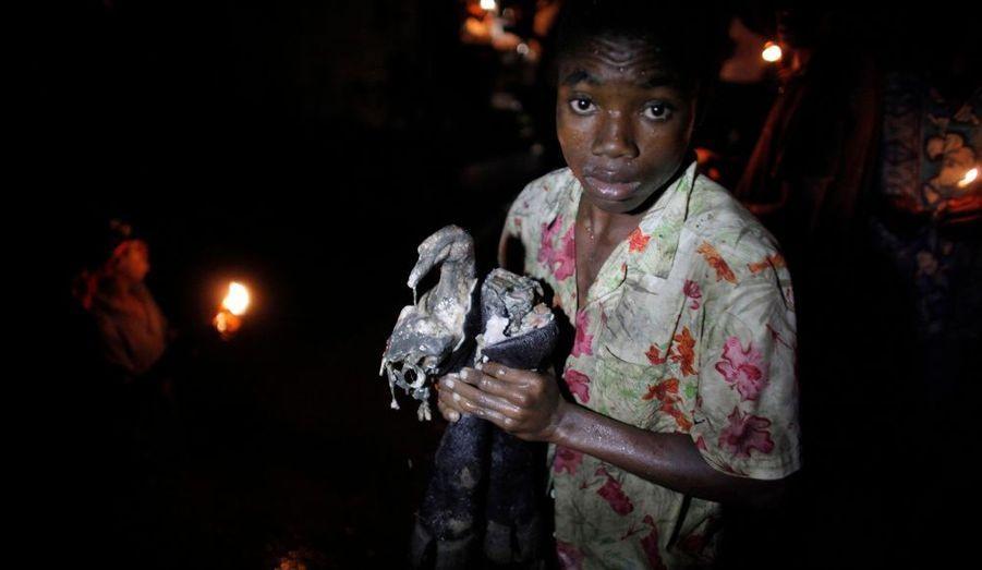 Un enfant tient dans ses mains des pieds de vache, après que l'animal ait été sacrifié lors d'un rituel de masse au cours du festival Plain Du Nord (Haiti). Des milliers de croyants sacrifient ainsi des animaux et prient dans des piscines de boue afin de demander aux esprits vaudous et aux morts de les aider financièrement, dans le futur et de protéger les enfants.