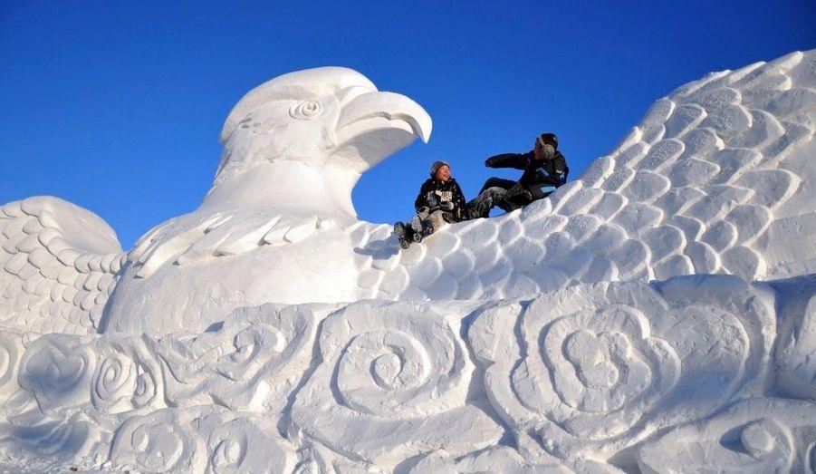 Des enfants jouent sur une sculpture, lors de la seconde édition du festival d'hiver de Naadam à Hulun Buir, en Mongolie.