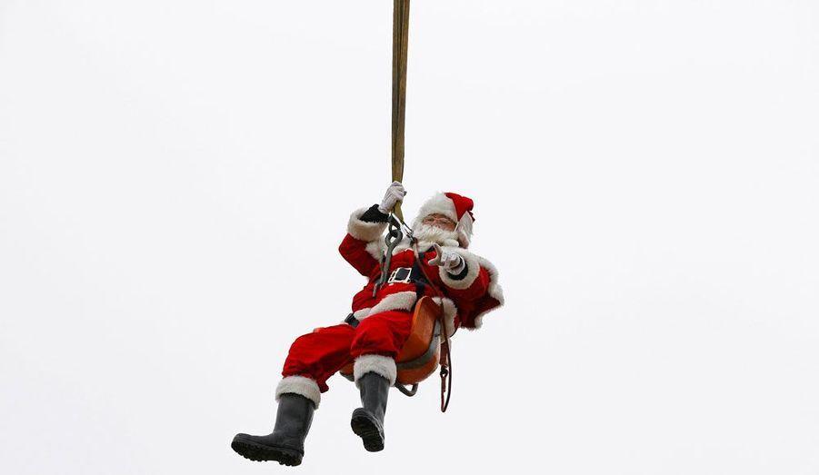Un Père Noël est hélitreuillé dans la première cheminée «compatible Père Noël» au monde, à Somerford Keynes, dans le Sud de l'Angleterre.
