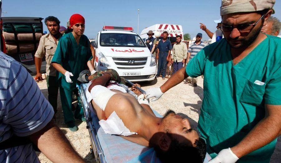 """Les forces du nouveau pouvoir libyen, appuyées par les avions de l'Otan, sont entrées samedi dans Syrte, ville natale du Guide déchu Mouammar Kadhafi et l'un de ses derniers bastions, où elles ont été accueillies par des tirs nourris de """"snipers"""". De la fumée noire tourbillonnait au-dessus de cette localité côtière alors que des forces du Conseil national de transition (CNT, au pouvoir) se massaient sur la place Zafrane, à un km du centre-ville. On pouvait entendre des fusillades du centre-ville au fur et à mesure de la progression des chars et des mortiers des """"katibas"""" (unités) du CNT. Des pick-up équipés de mitrailleuses et transportant des combattants se dirigeaient à toute vitesse vers Syrte. D'autres forces du CNT ont progressé à partir du sud de la ville. """"Ils ont posté des tireurs embusqués au-dessus des mosquées, des immeubles. Ils se servent aussi des maisons et des édifices publics"""", a raconté à l'envoyé spécial de Reuters un combattant, El Tohamy Abouzein, posté sur le rond point de la place Zafrane."""