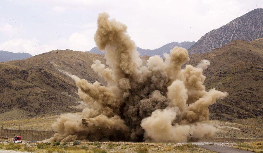 Sur la base d'opérations avancée Joyce, dans la province de Kunar, en Afghanistan, des pierres et des sacs de sable sont projetés en l'air lors de la destruction contrôlée d'une munition de mortier soviétique non explosée.