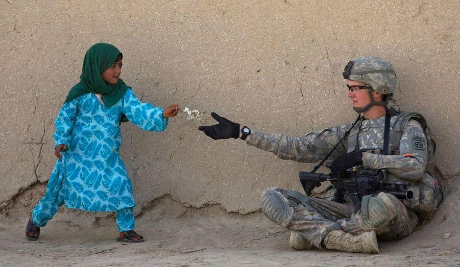 Un cadeau très touchant. Cette petite fille afghane offre une fleur à un soldat américain durant une patrouille dans la vallée d'Arghandab dans la province de Kandahar, dans le sud de l'Afghanistan.
