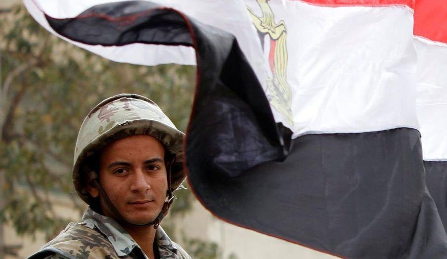 Un soldat égyptien, à côté d'un drapeau du pays sur la place Tahrir, au Caire.