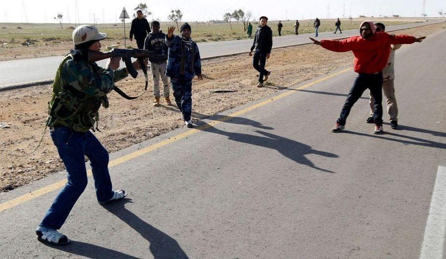 Sur la route entre Benghazi et Ajdabiyah, un rebelle libyen pointe son arme sur un homme qu'il suspecte d'être un pro-Kadhafi, alors qu'un autre insurgé met son corps en opposition pour le protéger.
