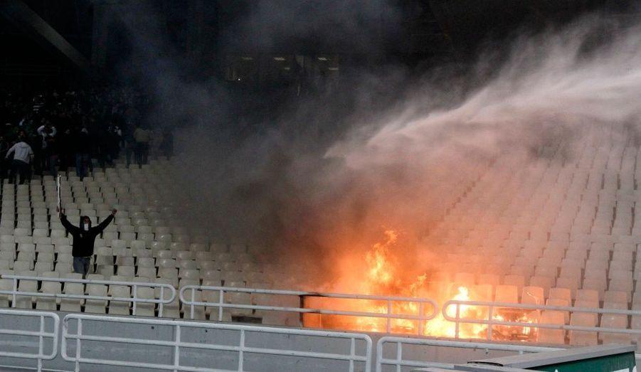 Un supporter célèbre le feu qui vient de prendre dans une tribune du stade olympique d'Athènes, lors d'un match de football.
