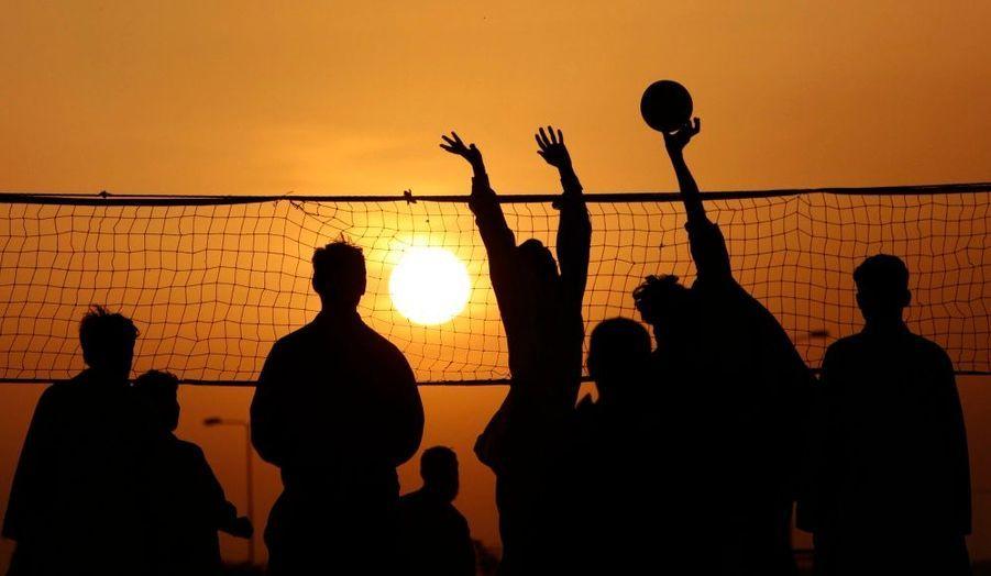 A la tombée de la nuit, des hommes jouent au volley-ball dans la capitale pakistanaise Islamabad.