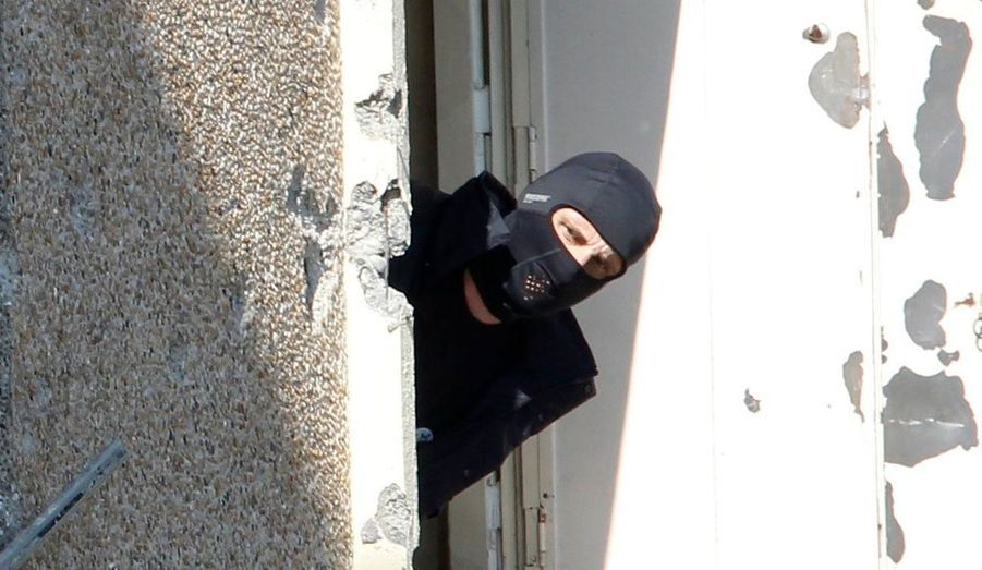Un policier regarde par la fenêtre de l'appartement de Mohamed Merah. L'analyse - et la polémique - continuent sur l'assaut donné contre le tueur de Toulouse.