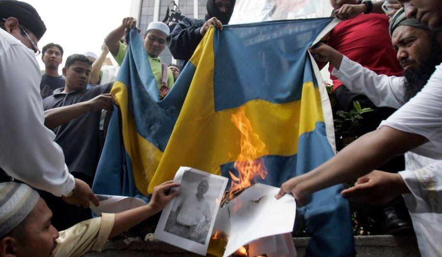 Des protestataires musulmans brûlent ostensiblement une photo de l'artiste suédois, Lars Vilks, plusieurs fois menacé pour avoir dessiné les caricatures de Mahomet en 2007.