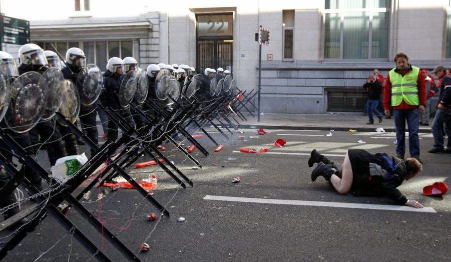 Un manifestant montre la partie charnue de son anatomie à des policiers anti-émeutes lors d'un défilé des Travailleurs européens et de représentants syndicaux. Des dizaines de milliers de personnes ont défilé à travers Bruxelles jeudi pour exhorter les dirigeants européens, réunis pour deux jours dans la capitale belge, à supprimer les mesures d'austérité.