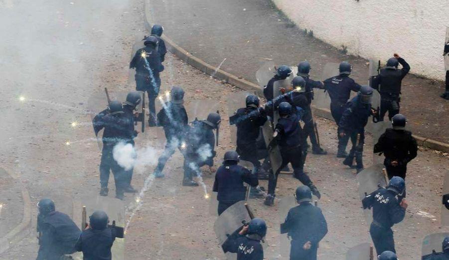 Des policiers tentent de se protéger de feux d'artifices lors d'une manifestation à Alger.
