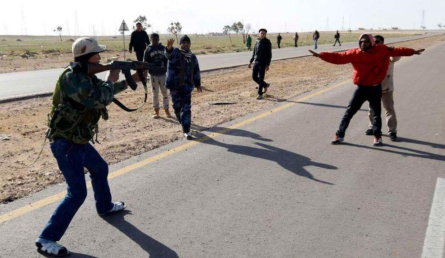 Scène de guerre civile à Ajdabiya en Libye. Un rebelle menace un présumé partisan de Kadhafi, alors qu'un autre insurgé s'interpose pour éviter un carnage.