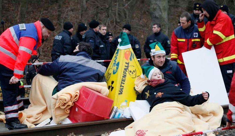 """Des centaines de militants anti-nucléaire ont passé la nuit de samedi à dimanche dans la région du Wendland, dans le nord de l'Allemagne, pour protester contre l'acheminement par le train de déchets radioactifs vers le centre de stockage de Gorleben. Des militants se sont enchaînés sur les rails par petits groupes, retardant l'avancée du convoi, toujours bloqué à une soixantaine de kilomètres de sa destination finale. Deux mille cinq cents activistes selon la police, 4.000 selon les militants du réseau Sortir du nucléaire, ont organisé un sit-in géant à Harlingen, un village situé sur la voie ferrée empruntée par le train """"Castor"""" entre Lüneburg et Dannenberg."""