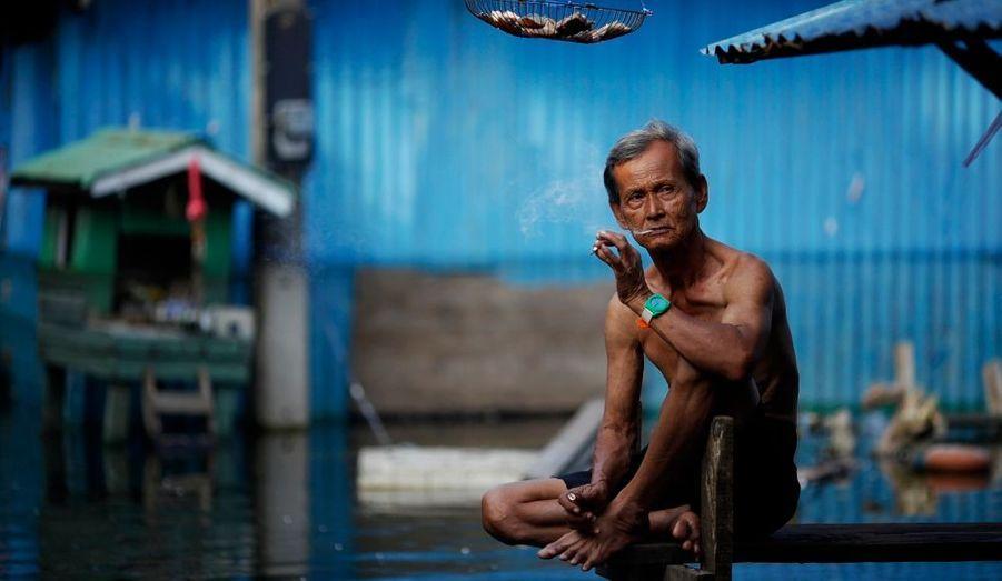 Un homme fume une cigarette devant sa maison inondée, dans un bidonville de Bangkok. Les intempéries ont fait plus de 500 morts et affecté plus de 2 millions de personnes depuis juillet en Thaïlande.