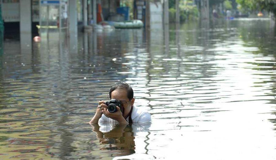 Un homme prend des photos dans les eaux de crue dans le quartier de Bang Khun Thian à Bangkok, en Thaïlande. Le nouveau bilan des inondations dévastatrices qui frappent le pays depuis trois mois fait état de 594 personnes morts et deux personnes toujours portées disparues.