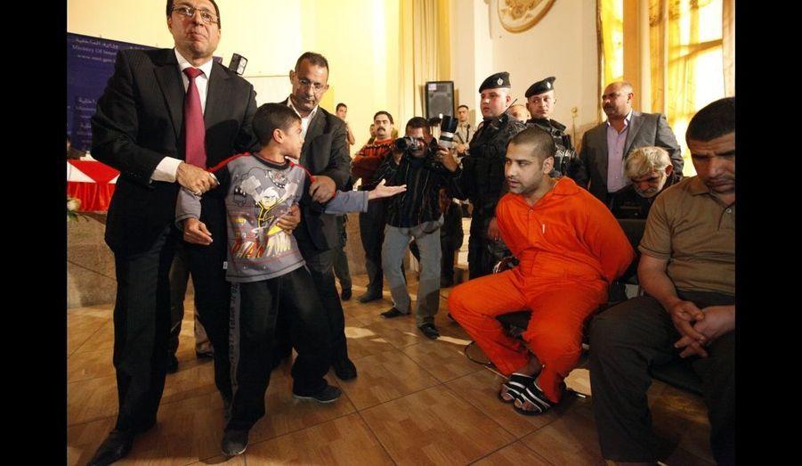 Un jeune garçon irakien est éloigné de l'homme qui estaccusé d'avoir tué son père, lors des massacres communautaires qui se sont déroulés entre 2006 et 2007. La scène se déroule lors de la présentation des 22 accusés à la presse, au ministère de l'Intérieur à Bagdad.
