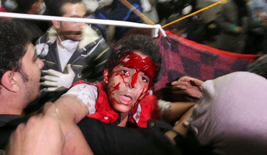 Un manifestant blessé est transporté à l'hôpital après de violents affrontements avec la police anti-émeute égyptienne place Tahrir, au Caire.