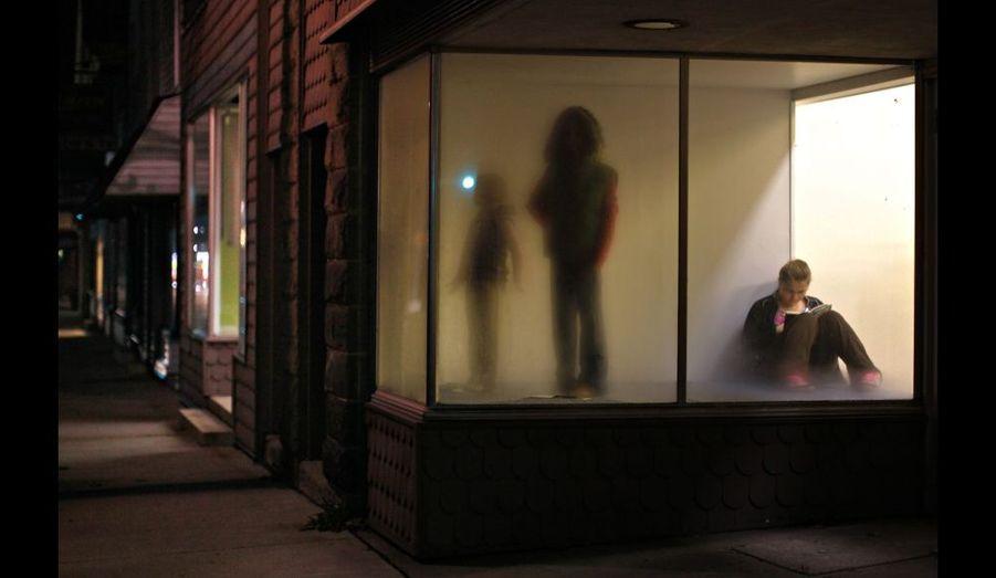 Une jeune femme lit un livre, assise dans la vitrine d'un magasin de New Bethlehem, en Pennsylvanie, aux États-Unis.