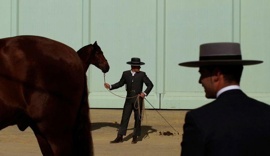 Des cavaliers attendent avec leur chevaux, avant le début d'une compétition équestre à Séville, en Espagne.