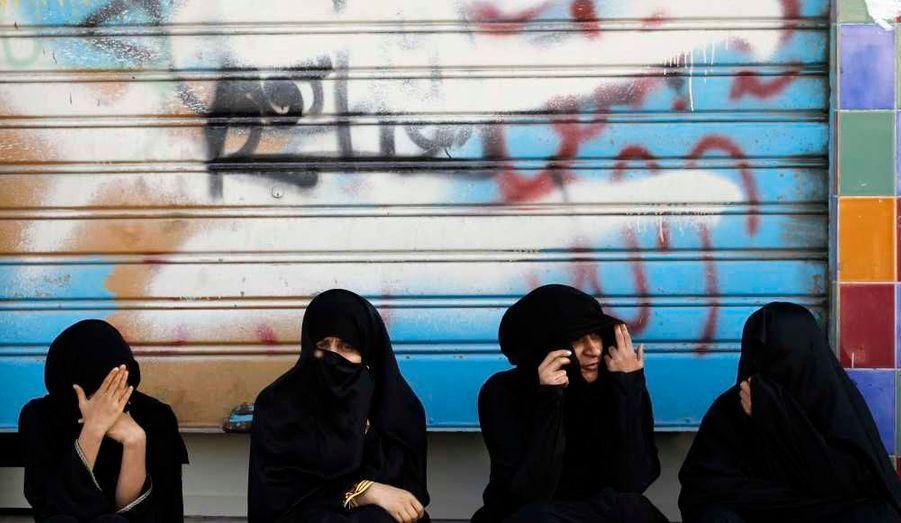 A Aali, au sud de Manama, des femmes regardent le cortège funèbre d'Abdulnabi Kadhum Akel, un chiite tué mercredi dans le cadre des manifestations qui secouent le pays depuis plusieurs mois. Les Bahreïnis, enhardis par une enquête sur les droits de l'Homme, démontrant des abus systématiques des autorités qui répriment le mouvement, se sont affrontés jeudi avec la police en marge des funérailles de cet homme.