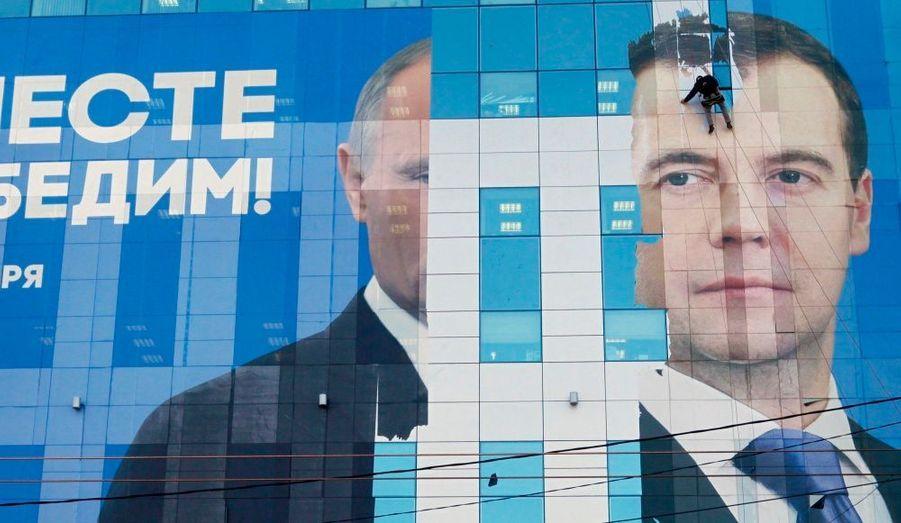 Un hommese charge de déployer une affiche pré-électoraleoù figurentle président russe Dmitri Medvedev et le Premier ministre Vladimir Poutine pour inciter les Russes à voterpour le parti Russie unie.