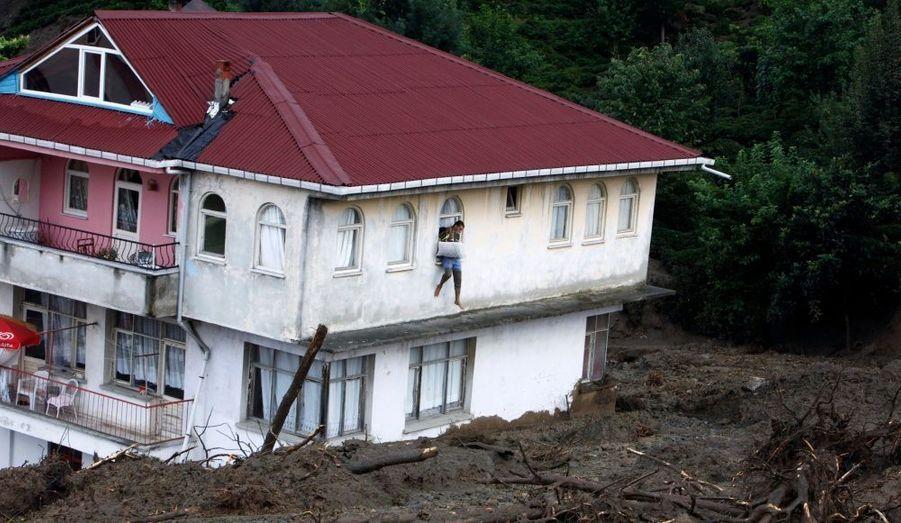 Un habitant portant une cage à oiseaux tente de quitter sa maison par une fenêtre: un glissement de terrain, provoqué par des pluies torrentielles, a balayé la ville de Gundogdu, dans la région Est de la Turquie, jeudi soir. Huit personnes ont été tuées et six autres sont portées disparues .