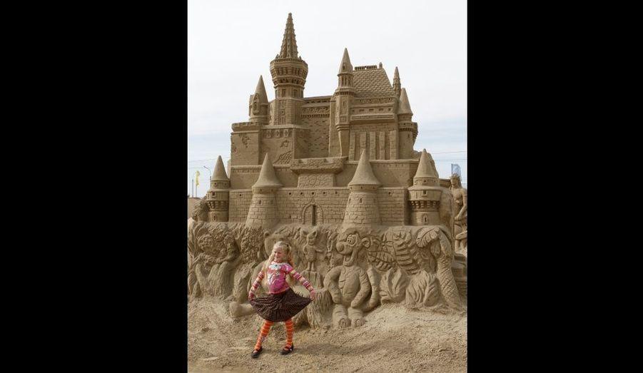 Une fillette pose devant une sculpture de sable sur le thème des personnages de Disney, dans la ville sibérienne de Krasnoïarsk, en Russie, hier.
