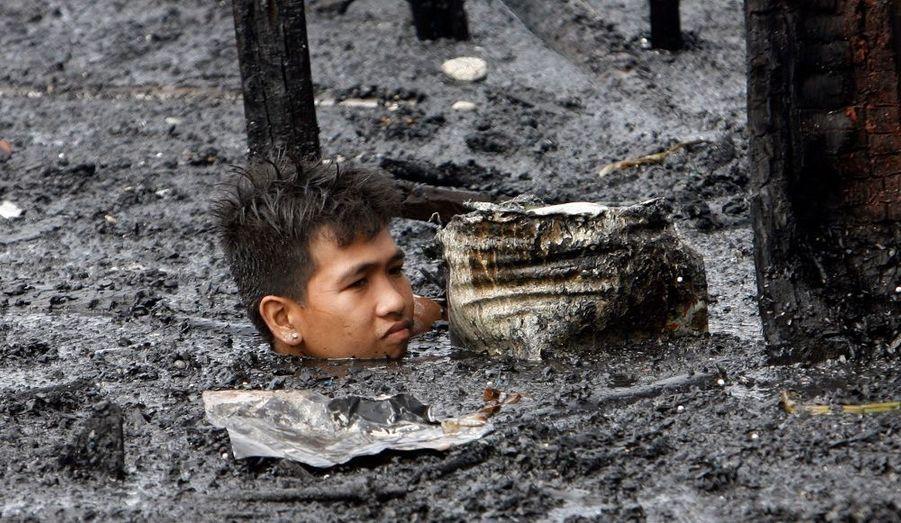 Ce garçon recherche des articles recyclables dans des eaux polluées. Jeudi soir, un incendie s'est déclaré dans un bidonville de le ville de Navotas, près de Manille, aux Philippines, endommageant 200 maisons, laissant 300 familles sans abri.