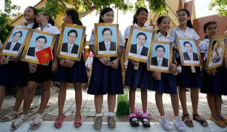 Des écolières cambodgiennes portent des portraits du président vietnamien Nguyen Minh Triet et du roi du Cambodge Norodom Sihamoni. Nguyen effectue une voyage officielle de trois jours au Cambodge pour renforcer les liens entre deux pays longtemps en conflit.