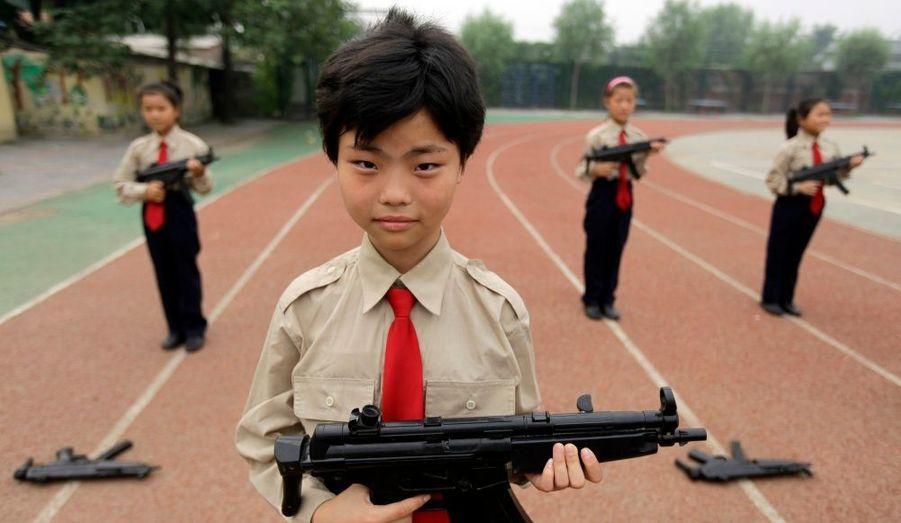 Ces élèves tiennent des armes, qui sont en fait de simples jouets. Ils se préparent pour une parade, afin d'accueillir des élèves venus de Hong Kong pour visiter leur école, qui accueille des travailleurs migrants.